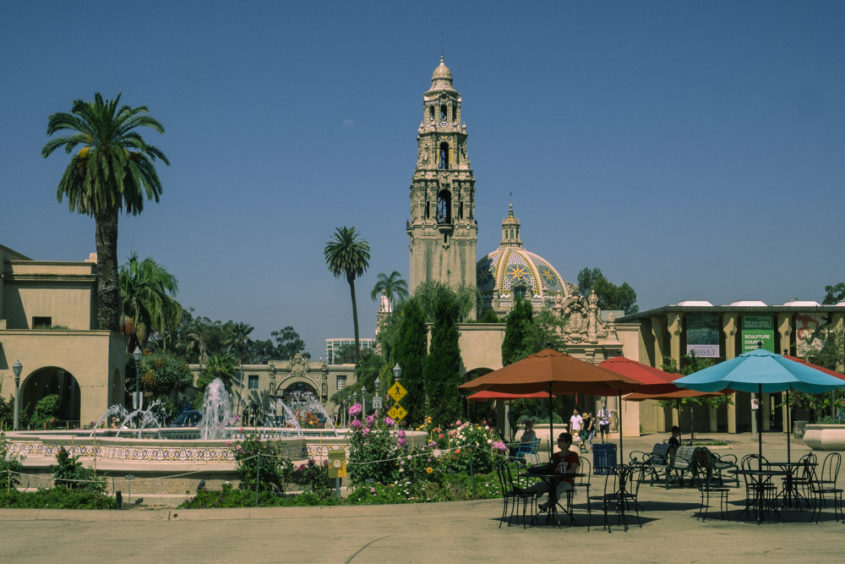 balboa park view with palm trees red umbrellas and people in front of a fountain