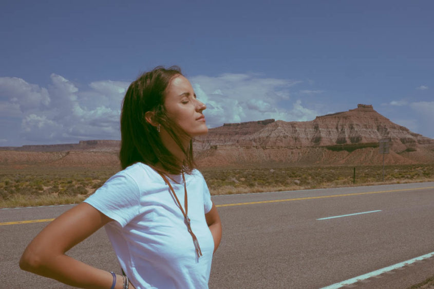 girl with eyes closed on empty american road with mountains