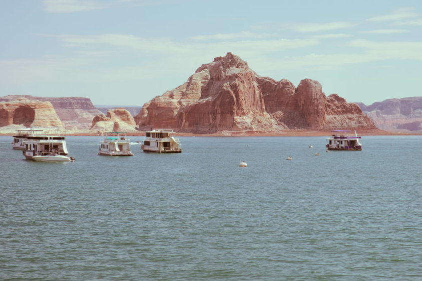boats on lake with red mountains