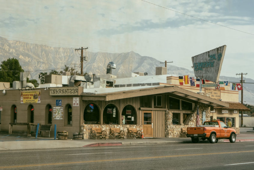 town with orange truck in front of restaurant and mountains in the background