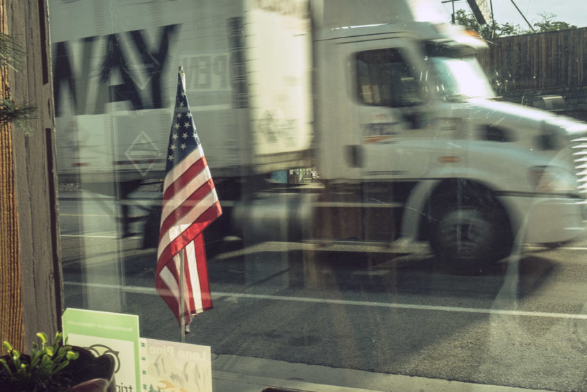 view from shop window of american flag and moving white truck