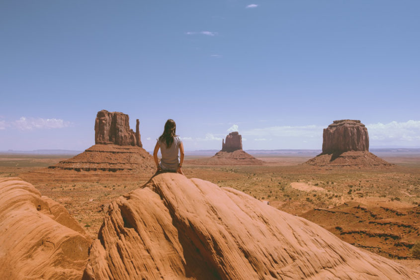 girl seating on rock looking at the monument valley view