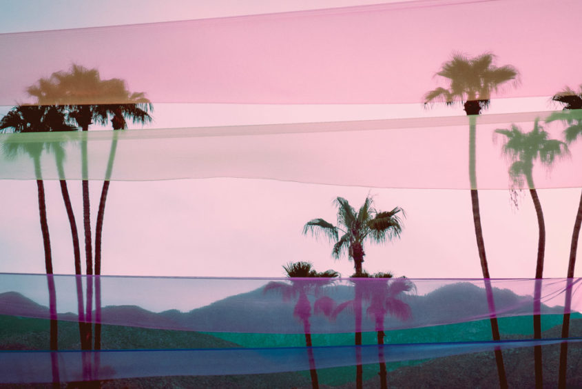 view of three sets of palms trees with the mountains in the back and coloured ribbons in the sky