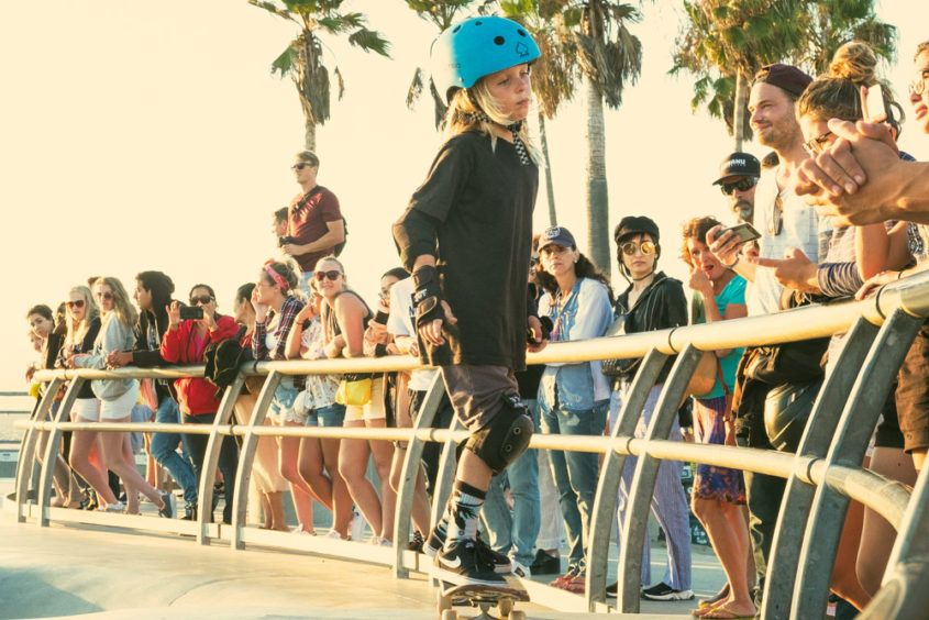 little blond girl with helmet at the venice beach skate park with people watching her