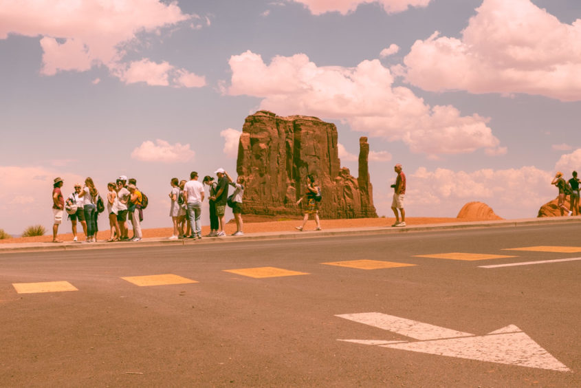 street with white arrow painted and yellow squares and tourists walking down red cliff