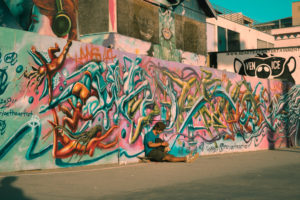 wall full of graffiti with skater sitting down