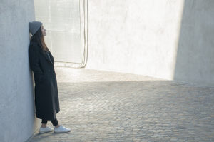 girl with black coat leaning against a white wall