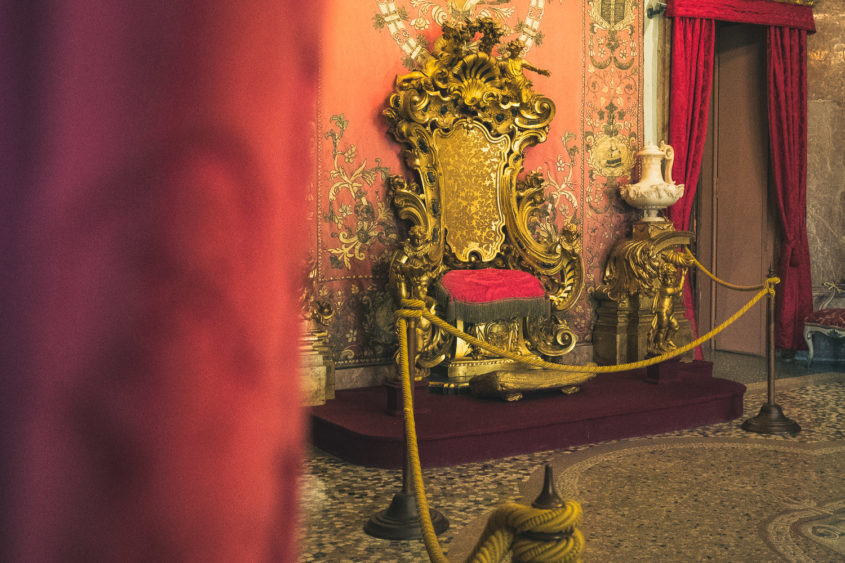 velvet red curtain and gold king's throne chair